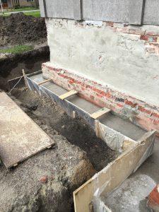 Het beton verbind de heipalen en de geboorde ankers.